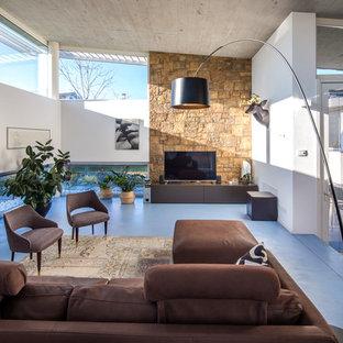 Esempio di un soggiorno contemporaneo aperto con libreria, pareti bianche, TV autoportante e pavimento blu