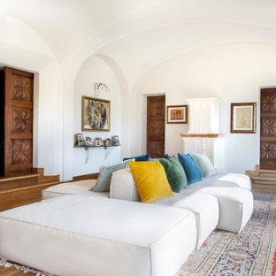 Idee per un ampio soggiorno mediterraneo aperto con parquet chiaro, cornice del camino in legno, nessuna TV, pavimento beige, soffitto a volta e pareti bianche