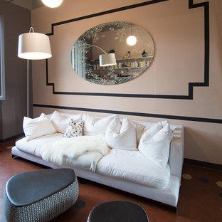 Modelo de sala de estar con biblioteca cerrada, tradicional renovada, pequeña, con paredes rosas, suelo de baldosas de terracota y televisor colgado en la pared
