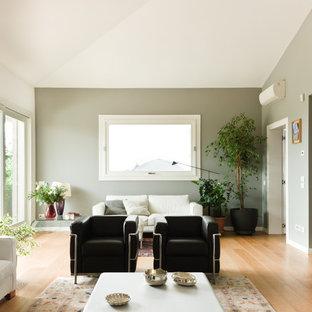 Idées déco pour une grand salle de séjour moderne avec un sol en bois clair, un téléviseur fixé au mur et un mur gris.