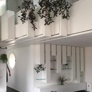 Foto di un soggiorno minimal di medie dimensioni e aperto con libreria, pareti bianche, pavimento in gres porcellanato, camino lineare Ribbon, cornice del camino in cemento e pavimento grigio