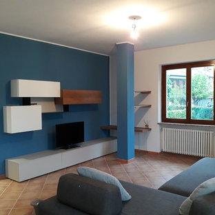 トゥーリンの中サイズのコンテンポラリースタイルのおしゃれなファミリールーム (青い壁、テラコッタタイルの床、埋込式メディアウォール、ピンクの床) の写真