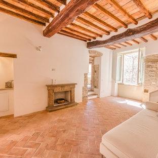 Imagen de salón cerrado, mediterráneo, de tamaño medio, con paredes blancas, suelo de baldosas de terracota, chimenea tradicional y marco de chimenea de piedra