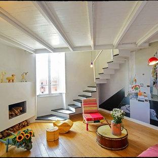 Esempio di un piccolo soggiorno bohémian con pareti multicolore, pavimento in legno massello medio, camino lineare Ribbon e cornice del camino in intonaco