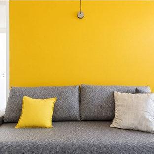 Esempio di un piccolo soggiorno minimalista aperto con pareti gialle, pavimento in gres porcellanato, parete attrezzata e pavimento grigio