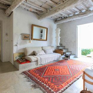 Ispirazione per un soggiorno mediterraneo aperto con pareti bianche, pavimento in cemento e pavimento grigio