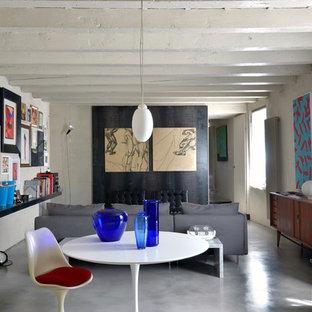 Immagine di un soggiorno eclettico chiuso e di medie dimensioni con pareti beige, pavimento in cemento, nessun camino, nessuna TV e pavimento grigio