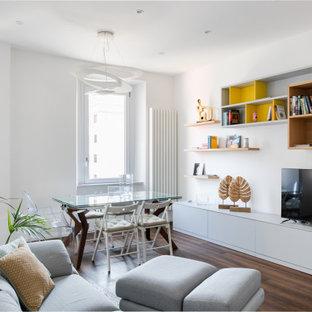 Immagine di un soggiorno design di medie dimensioni e aperto con pareti bianche, pavimento in legno massello medio, TV autoportante e pavimento marrone