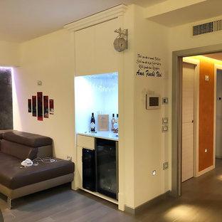 Esempio di un soggiorno minimal di medie dimensioni e aperto con angolo bar, pareti bianche, pavimento in gres porcellanato, TV a parete e pavimento marrone