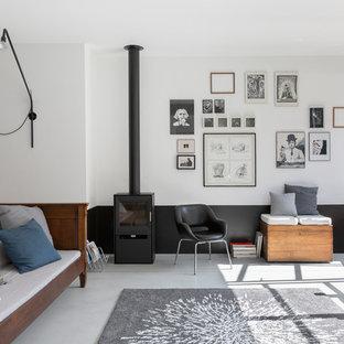 Imagen de salón abierto, industrial, extra grande, sin televisor, con paredes blancas, suelo de cemento, estufa de leña, marco de chimenea de metal y suelo gris