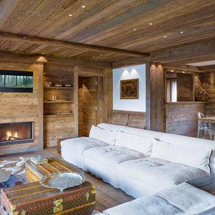 Esempio di un soggiorno rustico con parquet scuro, camino classico e cornice del camino in legno