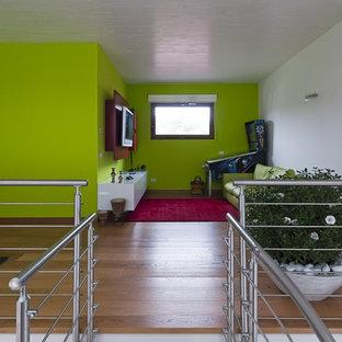 Ispirazione per un soggiorno country di medie dimensioni e stile loft con sala giochi, pareti verdi, pavimento in legno massello medio e TV a parete