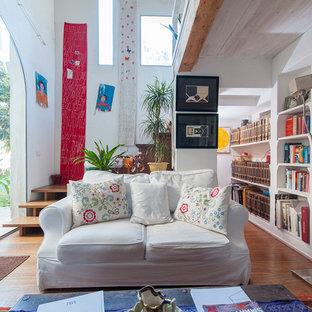 Idee per un soggiorno eclettico di medie dimensioni e aperto con libreria, pareti bianche, pavimento in legno massello medio e pavimento marrone