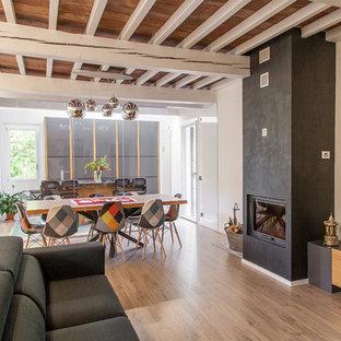 Ispirazione per un soggiorno design di medie dimensioni e aperto con pareti bianche, pavimento in legno massello medio, camino classico, pavimento marrone e TV autoportante