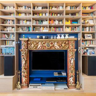 Immagine di un soggiorno mediterraneo con libreria, pareti blu, pavimento in legno verniciato e TV nascosta