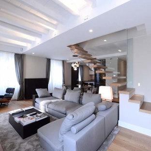 Foto di un grande soggiorno design aperto con pareti grigie e parquet chiaro