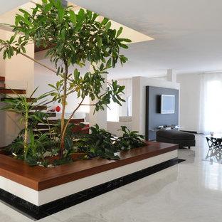 Immagine di un grande soggiorno design aperto con pareti bianche, pavimento in marmo e TV a parete