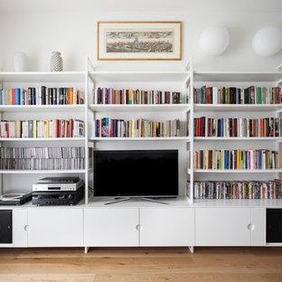 Idee per un soggiorno classico con libreria, pareti bianche, pavimento in legno massello medio, nessun camino, parete attrezzata e pavimento marrone