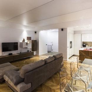 Immagine di un ampio soggiorno minimal aperto con sala formale, pareti bianche, pavimento in legno massello medio e TV a parete