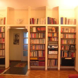 Idee per un soggiorno minimalista di medie dimensioni e aperto con libreria, pareti gialle e parquet chiaro
