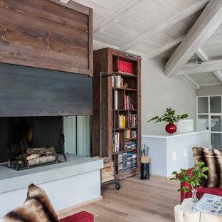 Immagine di un soggiorno country aperto e di medie dimensioni con pareti grigie, parquet chiaro, camino classico, cornice del camino in metallo, pavimento beige e libreria