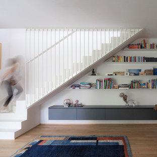 Esempio di un soggiorno design con pareti bianche, pavimento in legno massello medio, TV autoportante e pavimento marrone