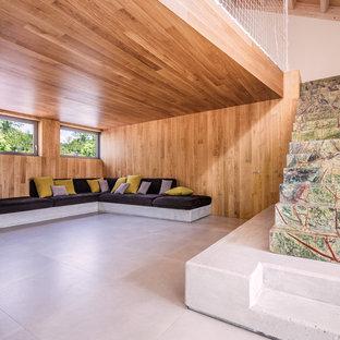 Esempio di un grande soggiorno stile rurale aperto con pavimento in gres porcellanato, TV nascosta, pareti marroni e pavimento grigio