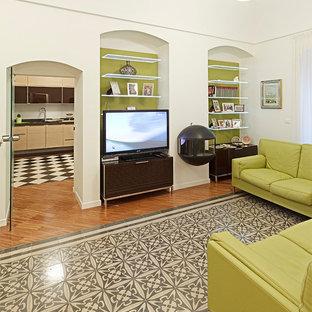 Idee per un grande soggiorno mediterraneo aperto con libreria, pareti bianche, pavimento in legno massello medio, camino sospeso, cornice del camino in metallo e parete attrezzata
