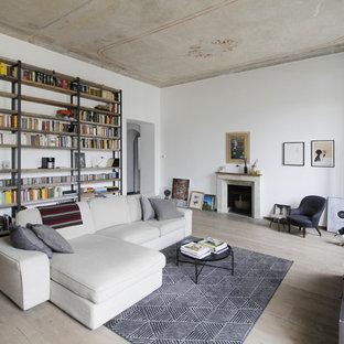 Idée de décoration pour un très grand salon avec une bibliothèque ou un coin lecture urbain fermé avec un mur blanc, une cheminée standard, un manteau de cheminée en pierre, un téléviseur indépendant, un sol en bois clair et un sol beige.