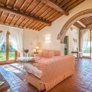 Diseño de sala de estar abierta, de estilo de casa de campo, grande, con suelo de baldosas de terracota, chimenea tradicional, marco de chimenea de yeso, televisor independiente y suelo rojo