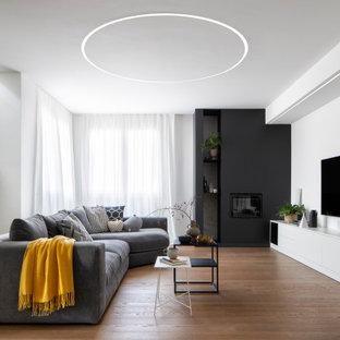 Ispirazione per un grande soggiorno design aperto con pareti bianche, parquet scuro, camino classico, cornice del camino in intonaco, TV a parete e pavimento marrone