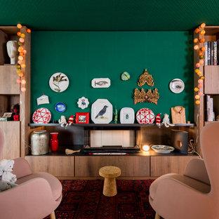 Immagine di un soggiorno boho chic aperto con libreria, pareti verdi, pavimento in legno massello medio, camino lineare Ribbon, cornice del camino in legno e TV autoportante
