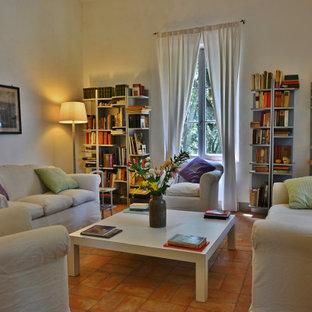 Foto de biblioteca en casa cerrada, moderna, grande, con paredes blancas, suelo de ladrillo, televisor retractable y suelo marrón