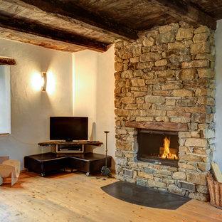 Esempio di un soggiorno in campagna aperto e di medie dimensioni con pareti bianche, pavimento in legno massello medio, camino classico, cornice del camino in pietra, TV autoportante e pavimento marrone