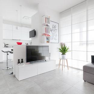Immagine di un soggiorno design aperto con pareti bianche, nessun camino, TV autoportante e pavimento grigio