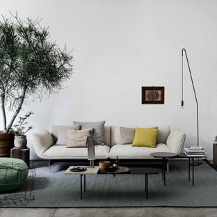 Immagine di un grande soggiorno minimal aperto con pareti bianche, pavimento in cemento e pavimento grigio