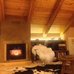 トゥーリンの大きいラスティックスタイルのおしゃれなファミリールーム (淡色無垢フローリング、横長型暖炉、漆喰の暖炉まわり、据え置き型テレビ、ベージュの壁) の写真