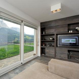 Immagine di un piccolo soggiorno minimal aperto con libreria, pareti multicolore, pavimento in legno massello medio, TV a parete e pavimento marrone