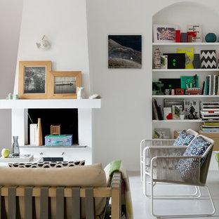 Esempio di un piccolo soggiorno contemporaneo aperto con pareti bianche, pavimento in cemento, camino classico, cornice del camino in intonaco e pavimento grigio