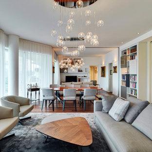 Esempio di un grande soggiorno design aperto con libreria, pareti bianche, pavimento in legno massello medio, TV autoportante e pavimento marrone