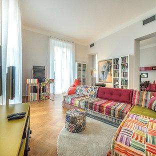 Immagine di un soggiorno eclettico aperto e di medie dimensioni con pareti grigie, parquet chiaro, parete attrezzata e pavimento marrone