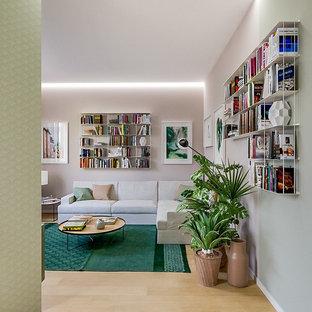 Esempio di un soggiorno design di medie dimensioni e aperto con libreria, parquet chiaro e pavimento beige