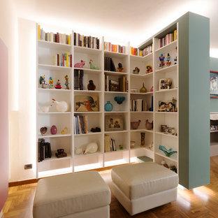 Foto di un soggiorno contemporaneo con libreria, pavimento in legno massello medio e pareti multicolore