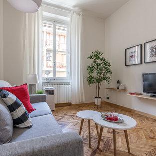 Immagine di un soggiorno design con pareti bianche, pavimento in legno massello medio, TV autoportante e pavimento marrone
