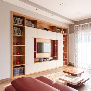 Foto di un ampio soggiorno contemporaneo aperto con libreria, pareti bianche, pavimento in gres porcellanato e TV a parete