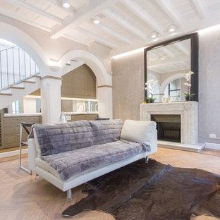Esempio di un piccolo soggiorno design aperto con pareti grigie, parquet chiaro, camino classico, cornice del camino in pietra, pavimento beige e TV a parete