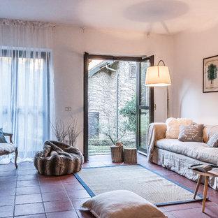 Idee per un soggiorno country con camino classico, cornice del camino in mattoni, pareti bianche e pavimento rosso