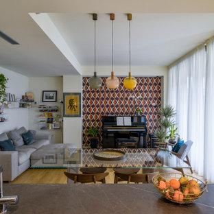 Idee per un piccolo soggiorno design aperto con pareti multicolore, pavimento in legno massello medio e pavimento marrone