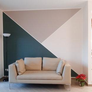 Diseño de salón abierto, contemporáneo, de tamaño medio, con paredes multicolor, suelo de baldosas de porcelana, televisor en una esquina y suelo beige