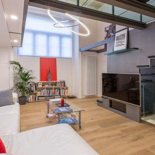 Foto di un soggiorno design aperto con pareti grigie, pavimento in legno massello medio, TV a parete e pavimento marrone